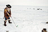 Male Golfer Dressed In Skin Attire Tees Off During The Bering Sea Ice Classic Golf Tournament, Nome, Arctic Alaska, Winter