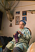 Portrait Of Female Native Yupik Elder Sitting In Living Room Knitting Akiachak We Alaska Indoors