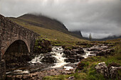 'Low Clouds Over A Landscape With A Stream Cascading Over Rocks And Under A Bridge; Applecross Peninsula Scotland'