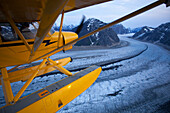 A pilot flies his Super Cub floatplane over the Ruth Glacier valley with Alaska Range in the background, Summer, Southcentral, Alaska