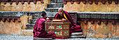 'China, Xizang, Tibet, Two Monks sitting together inside Walls of Sera Monastery; Lhasa'