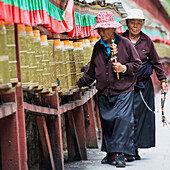 'China, Xizang, Women Walking Together along Prayer Wheels at Potala Palace; Tibet'