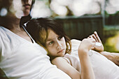 'Girl Cuddling Against Her Mother On A Chair In The Backyard;Otterburn Park Quebec Canada'
