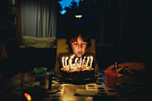 'Young Boy Blowing Candles On Birthday Cake In The Dark;Otterburn Park Quebec Canada'