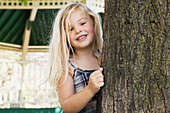'Young Blonde Girl Smiling And Looking Out From Behind A Tree;Ontario Canada'