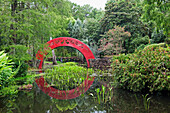 'Usa, Alabama, Red Arched Bridge Crossing Tranquil Water In Park; Mobile'