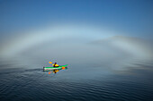A sea kayaker paddles along the edge of a thick fog bank in Southeast Alaska's Stephens Passage, a fog bow has formed where water particles reflect the light of the morning sun. MR_ Ed Emswiler, ID#12172012A