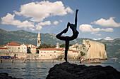 Sculpture of a nude female acrobat in front of the old town of Budva, Stari Grad, Adriatic coastline, Montenegro, Western Balkan, Europe