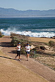 South Africa, Couple running along shore, Mossel Bay