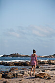South Africa, Young woman walking along seashore, Mossel Bay