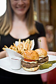 USA, New York State, Waitress with fries and hamburger in Cinema Restaurant, New York City
