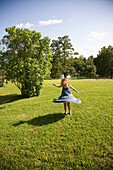 USA, New York State, Girl spinning on green grass, Hudson Valley