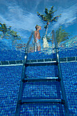 Man walking past steps to swimming pool, Ocean Blue Hotel, Punta Cana, Dominican Republic. © Ian Cumming / Axiom
