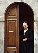 Lady In Traditional Dress Standing In The Doorway Of Her House, Scanno, Abruzzo, Italy.