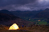Lit tent on hill above Langdale on stormy evening, Lake District, Cumbria, England