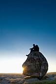 Man Sitting On Head-Shaped Boulder At Dusk, Twisleton Scars, Near Ingleton, Yorkshire Dales National Park, North Yorkshire, England.