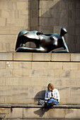 United Kingdom, England, West Yorkshire, Henry Moore sculpture outside Leeds Art Gallery and woman reading book beneath, Leeds