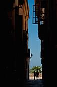 Couple walking along narrow alley, Palma, Majorca, Spain