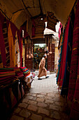 Looking past clothes for sale in narrow passageway to man walking up alley, Fez, Morocco
