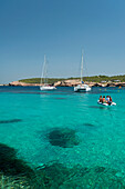 People in small boat going out to their yacht off Cala Bassa Beach, Ibiza, Spain