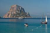 People on boats off Cala d'Hort beach with Es Vedra Island behind, Ibiza, Spain