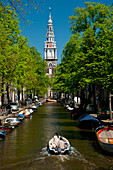Couple in boat going along canal with spire of Zuiderkerk Church in background, Amsterdam, Holland