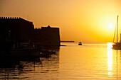 Fishing boat, harbor and Venetian fortress at dawn, Heraklion, Crete, Greece