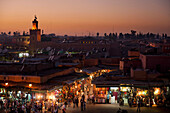 Looking over entrance to souks at dusk at edge of Djemaa El Fna, Marrakesh, Morocco