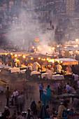 People and food stalls in Djemaa el Fna at dusk, Marrakesh, Morocco