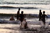 India, Karnataka, Blurry figures in crashing waves at Gokarna beach, Gokarna