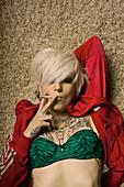 Blonde Women With Tattoos Lying On Carpet Smoking