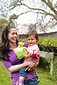Mother And Daughter With Watering Can In Outside Garden, Vancouver British Columbia
