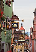Colorful sign ornaments on top of each shop or restaurant, Rothenburg ob der Tauber, Bavaria, Germany