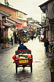 Woman rides tricycle with vegetables on Old City Dali streets, Dali City, Yunnan, China