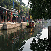 A boat in the tranquil river water and buildings along the water's edge, Beijing, China