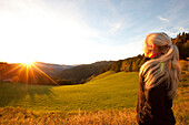 Young woman enjoying sunrise, Styria, Austria