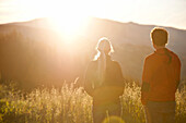 Couple looking at a sunrise above an alpine pasture, Styria, Austria