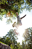 Young man jumping, Styria, Austria