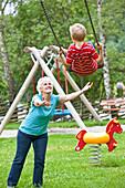 Großmutter und Enkelsohn (7 Jahre) auf einem Spielplatz, Steiermark, Österreich