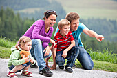 Family crouching on a path, Styria, Austria