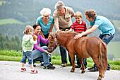 Großfamilie streichelt ein Pony, Steiermark, Österreich