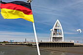 German flag at Juist harbour with observation tower in the background, landmark, Juist Island, Nationalpark, North Sea, East Frisian Islands, East Frisia, Lower Saxony, Germany, Europe