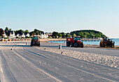 Tractors cleaning the beach, Travemuende, Luebeck, Schleswig-Holstein, Germany