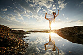 Woman practicing yoga at lake Starnberg, Upper Bavaria, Germany