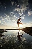 Man practicing acro yoga at lake Starnberg, Upper Bavaria, Germany