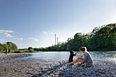 Woman playing with a dog at river Isar, Wittelsbach bridge, Munich, Bavaria, Germany