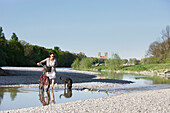 Woman with bicycle and a dog on a gravel bank in river Isar, Munich, Bavaria, Germany