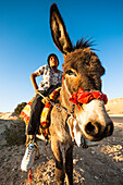 Boy riding a donkey, Wadi Musa, Jordan, Middle East