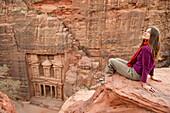 Frau sitzt auf einem Felsen, Khazne al-Firaun im Hintergrund, Petra, Jordanien, Naher Osten