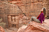 Woman sitting on a rock, Al Khazneh in background, Petra, Jordan, Middle East